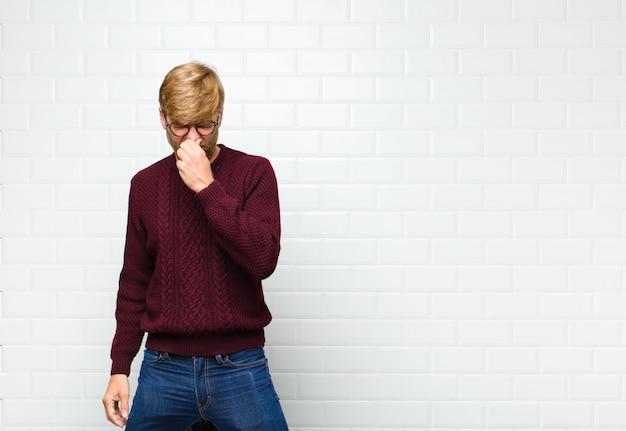Sentindo-se enojado, segurando o nariz para evitar cheirar um fedor desagradável e desagradável Foto Premium