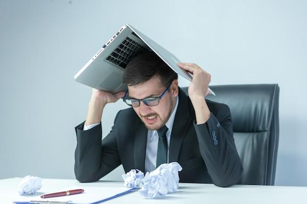 Sentindo-se exausto. homem jovem frustrado, mantendo os olhos fechados e parecendo cansado enquanto trabalhava até tarde no local de trabalho. Foto Premium