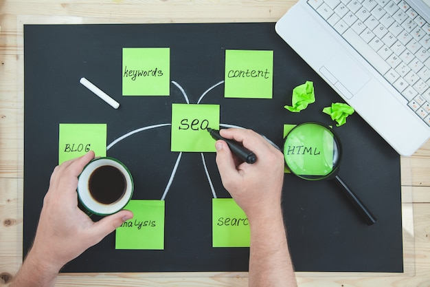 Seo search engine optimization notas de papel em um fundo escuro com inscrições Foto Premium