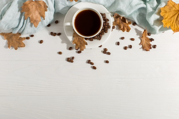 Seque as folhas amarelas, lenço azul, grãos de café e uma xícara em uma mesa branca, dia de início de manhã. fundo do humor do outono, copyspace, configuração lisa. Foto Premium