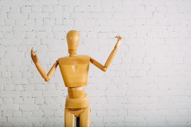 Ser humano de madeira na parede de tijolo branco com espaço da cópia Foto Premium