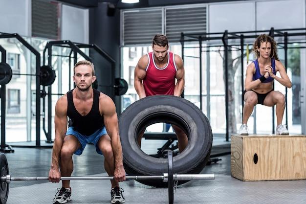 Séria três pessoas musculares levantando e pulando Foto Premium