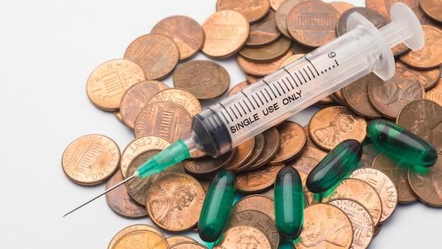 Seringa e cápsula verde droga na pilha de moedas de 1 cent, o símbolo do custo de saúde Foto Premium