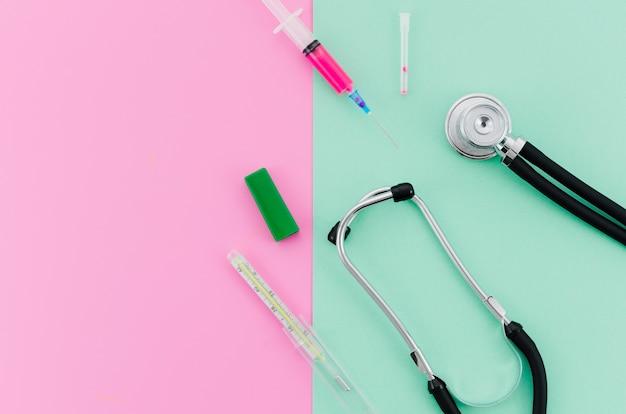 Seringa; estetoscópio; termômetro no fundo verde rosa e menta Foto gratuita