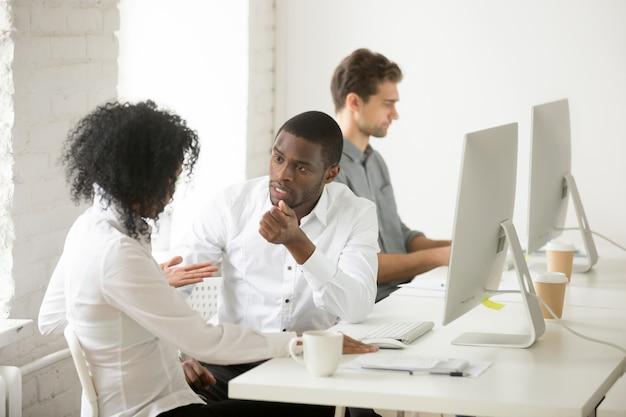 Sério, americano africano, colegas, falando, discutir, projeto, junto, em, local trabalho Foto gratuita