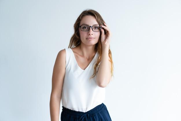 Sério bela dama, ajustando os óculos e olhando para a câmera Foto gratuita