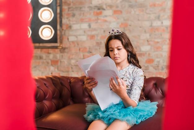 Sério, cute, menina, sentando, ligado, sofá, leitura, scripts, em, backstage Foto gratuita