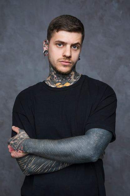 Sério homem jovem tatuado com piercing em seus ouvidos e nariz, olhando para a câmera Foto gratuita