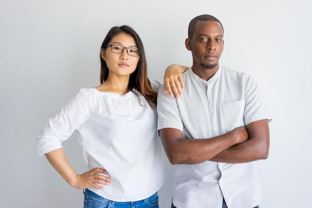 Sério jovem casal multiétnico confiante, olhando para a câmera e em pé no estúdio Foto gratuita
