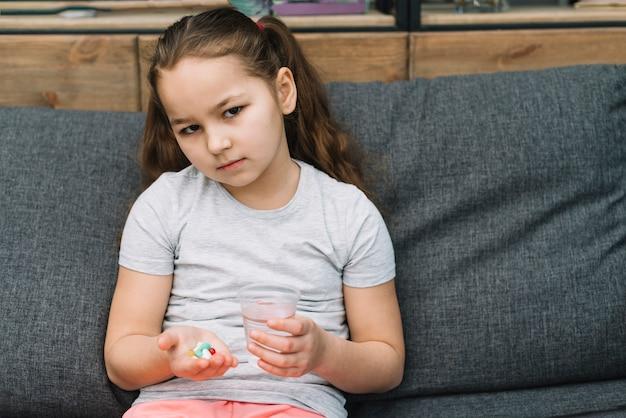 Sério menina sentada no sofá segurando pílulas e copo de água na mão Foto gratuita