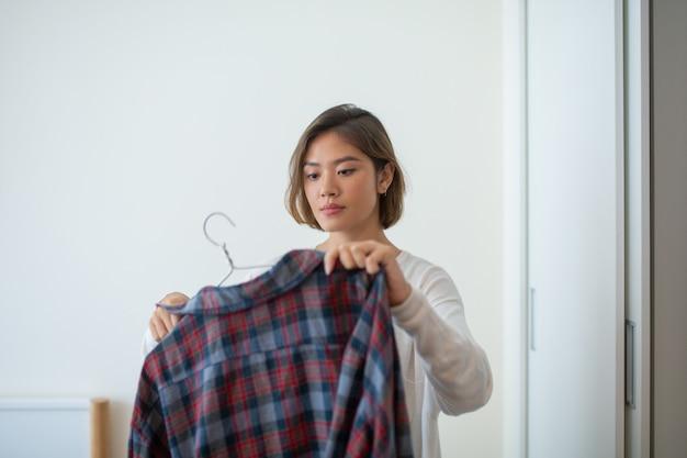Sério muito jovem mulher pendurada camisa no cabide em casa Foto gratuita