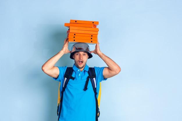 Serviço de entrega sem contato durante a quarentena. homem entrega comida e sacolas de compras durante o isolamento. emoções do entregador isoladas em azul Foto gratuita