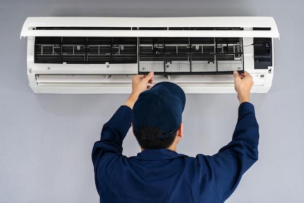 Serviço técnico remover o filtro de ar do ar condicionado para limpeza Foto Premium
