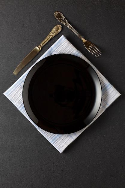Servindo em um restaurante luxuoso. prato vazio preto e utensílios de prata. Foto Premium