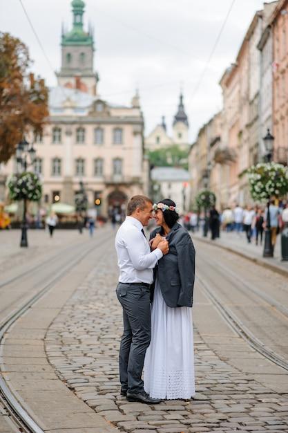 Sessão de fotos de casamento no centro da cidade velha. o noivo deu a sua noiva sua jaqueta para que ela se aquecesse. o casal abraça e sorri um para o outro. fotografia de casamento em estilo rústico Foto Premium