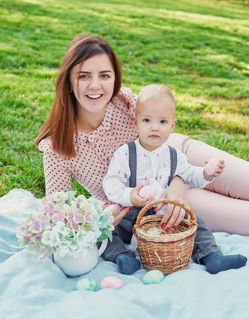 Sessão de fotos em família de mãe e filho para páscoa no parque, ao lado deles é uma cesta com ovos e um coelho da páscoa Foto Premium