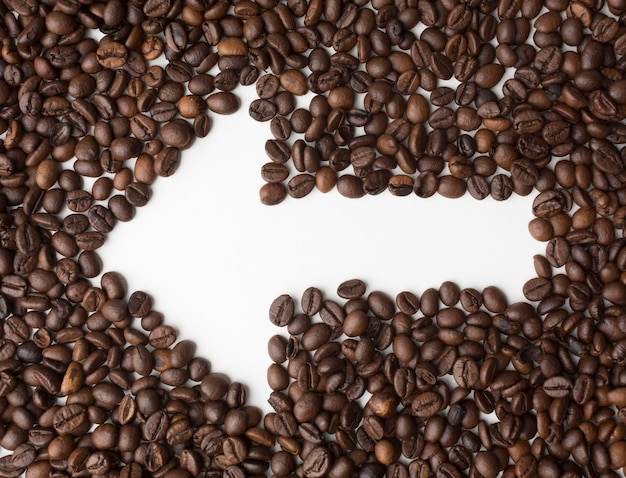 Seta através de grãos de café, apontando para a esquerda Foto gratuita