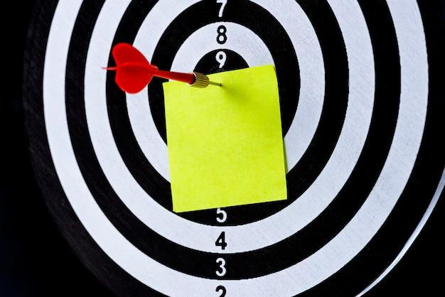 Seta de dardo vermelho, atingindo o centro do alvo com notas em branco no tabuleiro de dardo Foto Premium