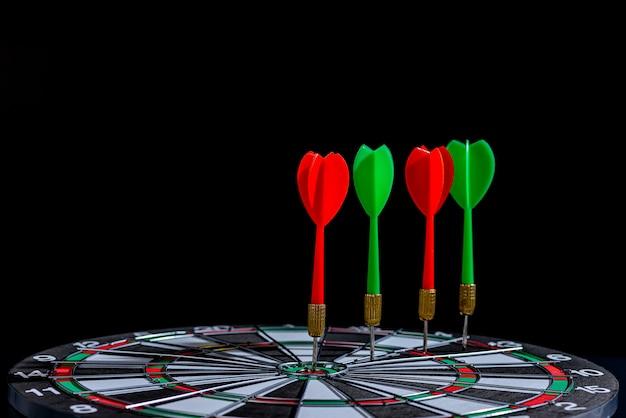 Seta de dardo vermelho e verde, atingindo o centro do alvo Foto Premium