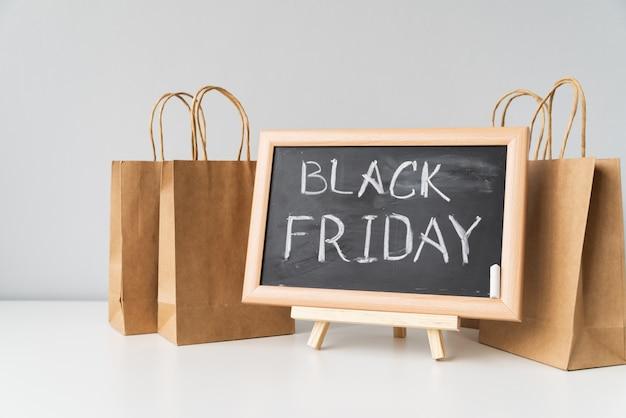 Sexta-feira negra, escrita no quadro-negro com sacos de compras Foto gratuita