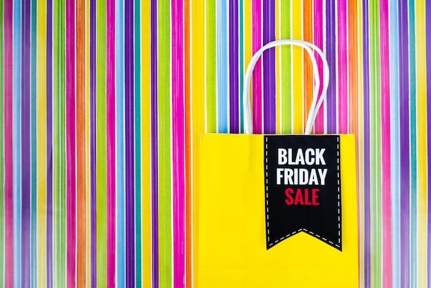 Sexta-feira negra saco de compras em fundo colorido Foto gratuita