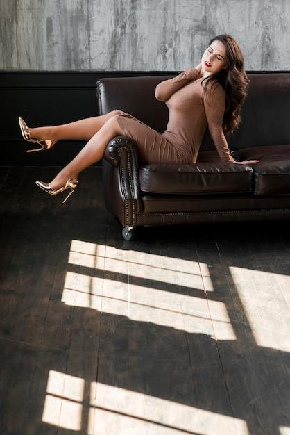 Sexy jovem vestindo saltos altos dourados sentado no sofá Foto gratuita