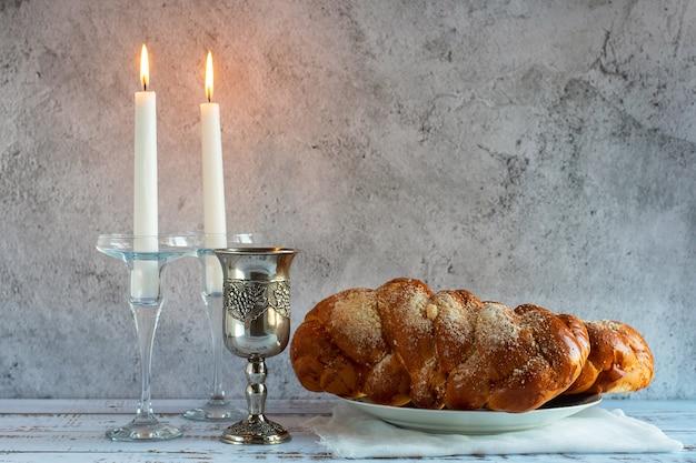 Shabat shalom - pão chalá, vinho shabat e velas na mesa de madeira Foto Premium