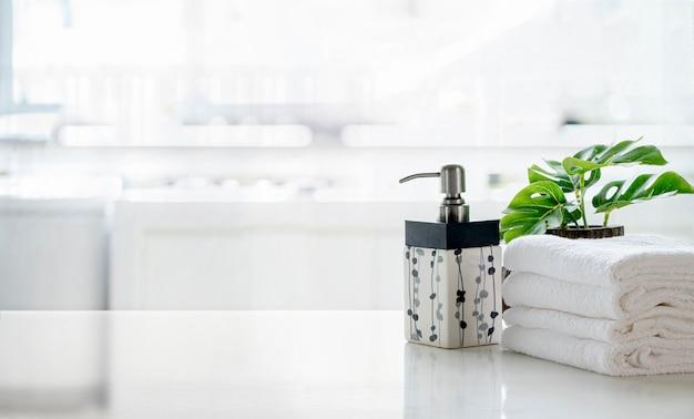 Shampoo cerâmico, frasco de sabão e toalhas no balcão da cozinha. espaço superior branco da tabela e cópia. Foto Premium