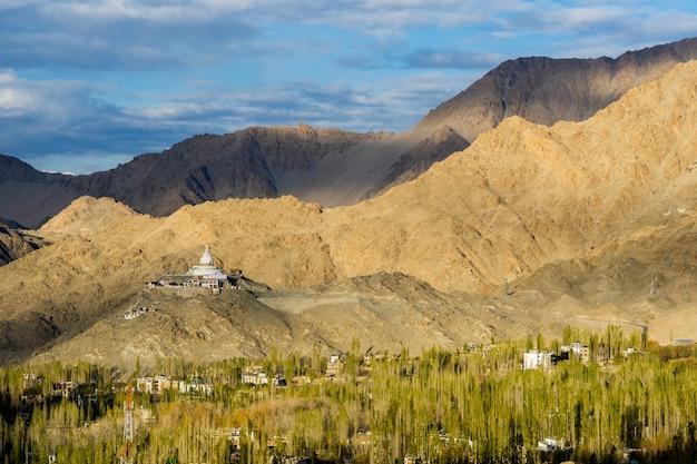 Shanti stupa com a grande montanha no fundo e a cidade de leh com outono dourado da folha Foto Premium