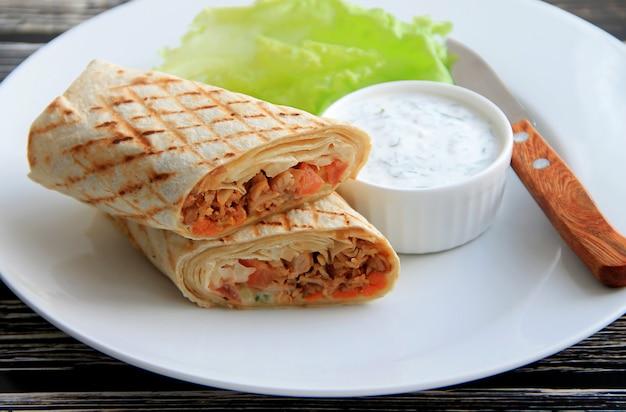 Shawarma com frango, legumes e ervas em um prato branco ao lado do molho e faca Foto Premium