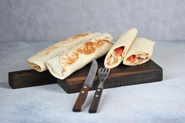 Shawarma de frango na tábua de madeira Foto Premium