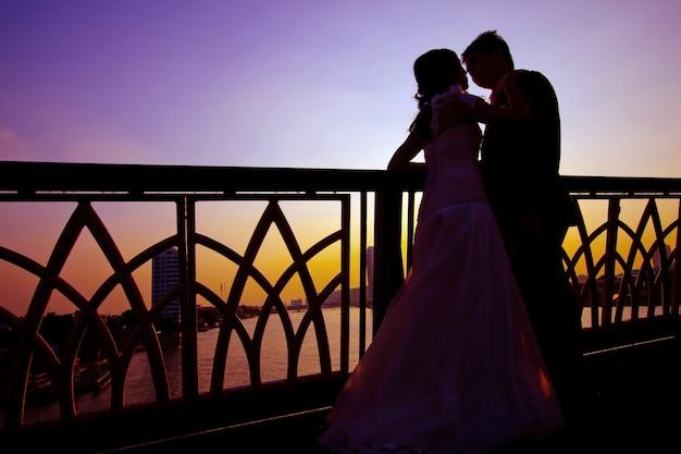 Shilhouette de casais românticos e felicidade na ponte sobre o rio Foto Premium