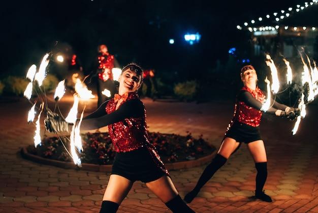 Show de fogo. dançarinas de meninas giram tochas de fogo. Foto Premium