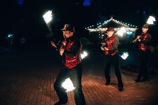 Show de fogo. dançarinos masculinos giram tochas de fogo Foto Premium