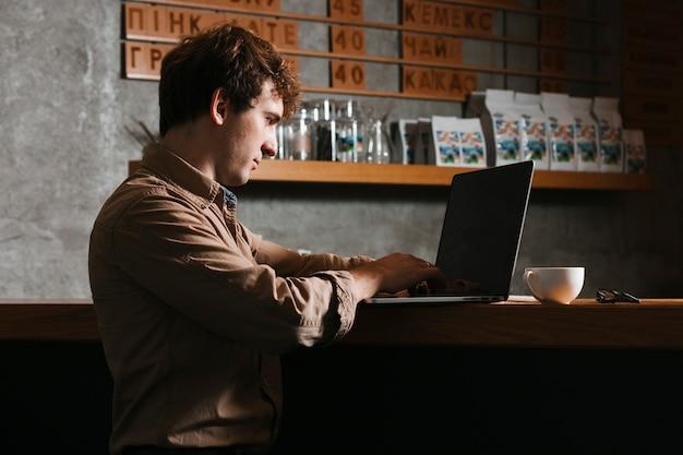 Sideview homem trabalhando no laptop no escritório Foto gratuita