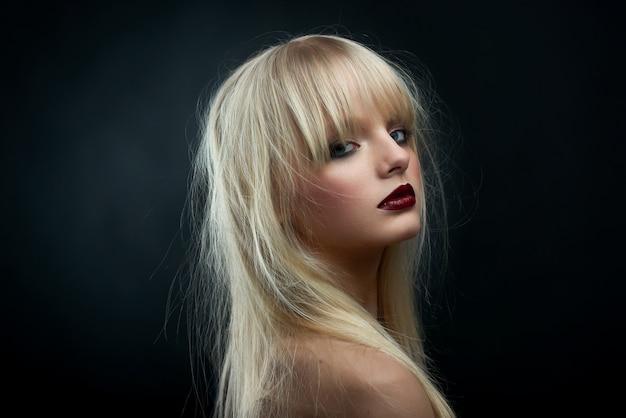 Sideview horizontal da menina loura que desgasta o batom vermelho. Foto Premium
