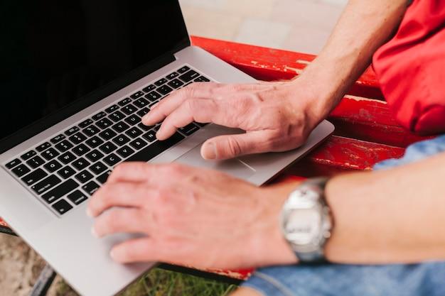 Sideview mãos no teclado do laptop Foto gratuita