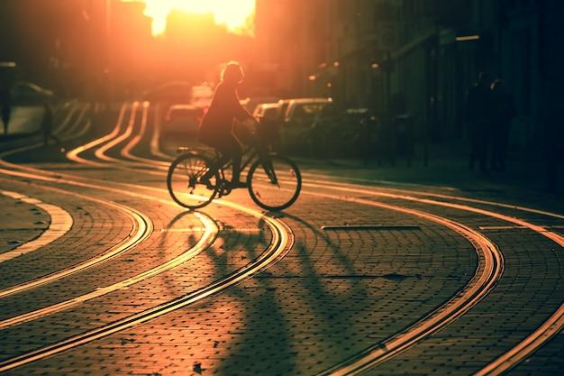 Silhueta borrada de bicicleta de equitação de mulher durante o pôr do sol na cidade de bordeaux em estilo vintage Foto Premium