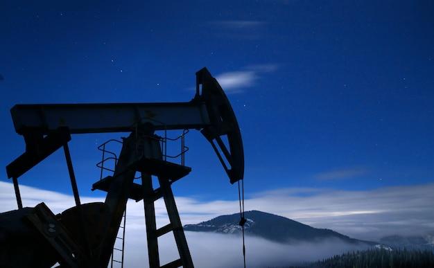Silhueta da bomba de óleo à noite. Foto gratuita