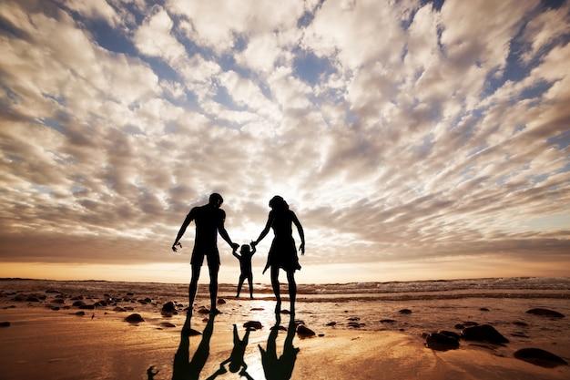 Silhueta da família que joga na praia Foto gratuita