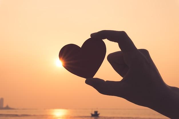 Silhueta da mão que prende o coração vermelho durante o fundo do por do sol. Foto Premium