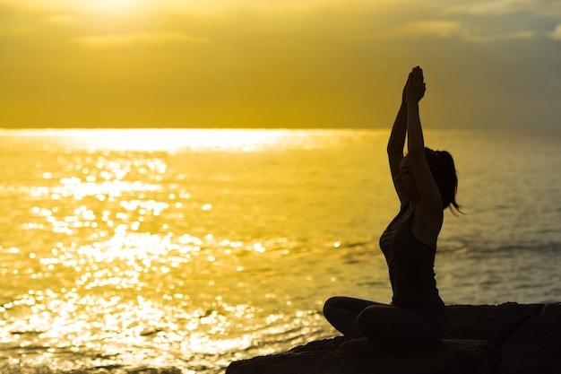 Silhueta da mulher nova que meditating e que pratica a ioga na praia no por do sol. Foto Premium
