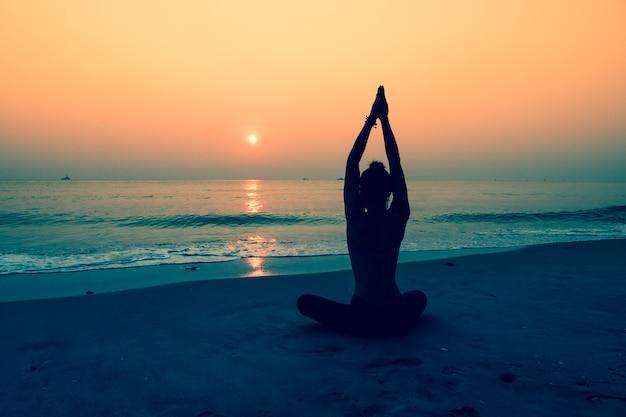 Silhueta da mulher que faz a ioga em uma praia Foto gratuita