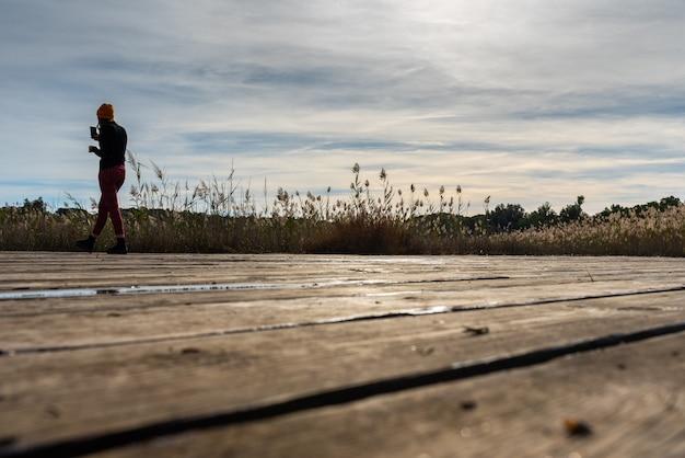 Silhueta da mulher que toma uma foto com seu móbil de uma paisagem mediterrânea. Foto Premium