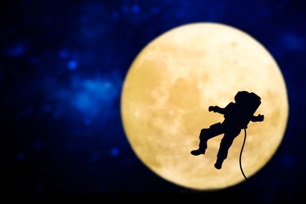 Silhueta de astronauta sobre a lua cheia Foto gratuita