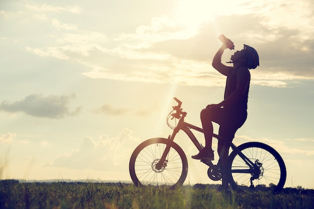 Silhueta de ciclismo de descanso e bebendo da água do ciclista no por do sol. Foto Premium