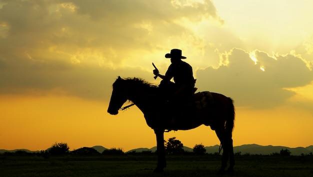 Silhueta de cowboy cavalo contra o pôr do sol no campo Foto Premium