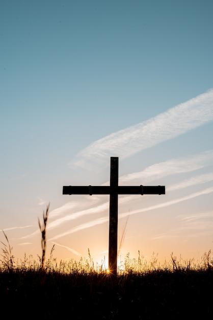 Silhueta de cruz de madeira em um campo gramado com um céu azul ao fundo em um tiro vertical Foto gratuita
