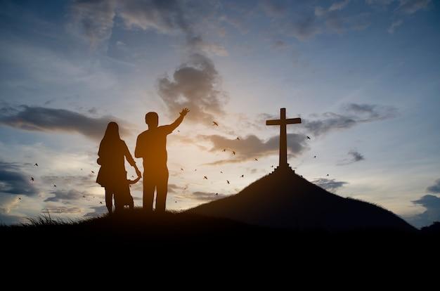 Silhueta de família cristã em pé com uma cruz para adorar a deus Foto Premium