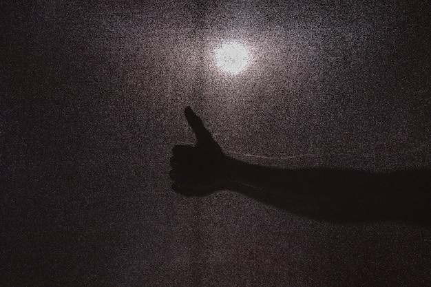 Silhueta de mão gesticulando polegar para cima Foto gratuita